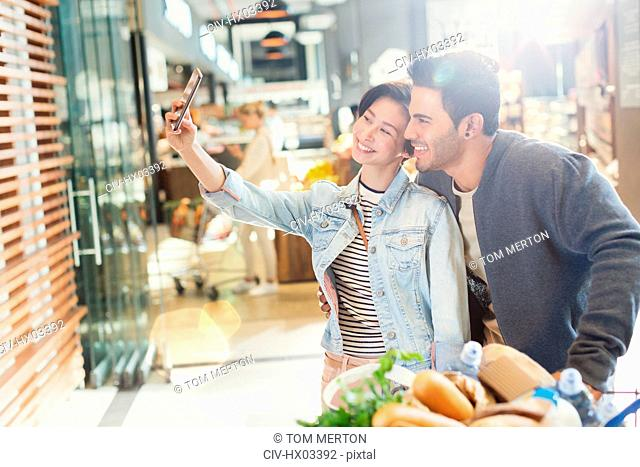 Young couple taking selfie grocery shopping in market