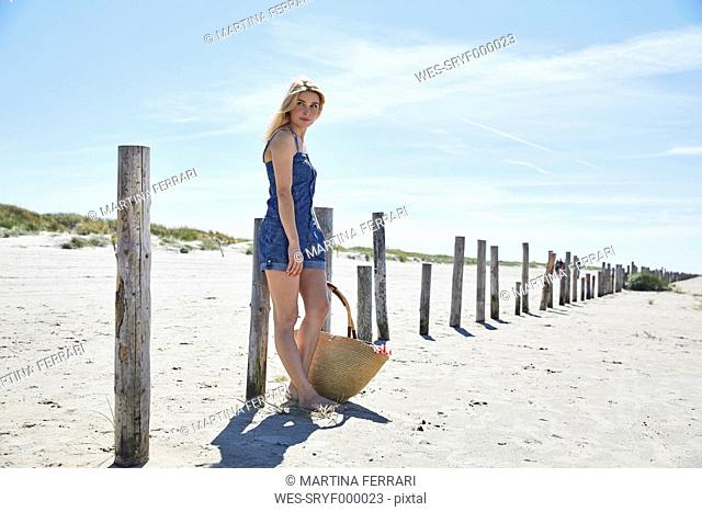 Young woman waiting at wooden poles on the beach
