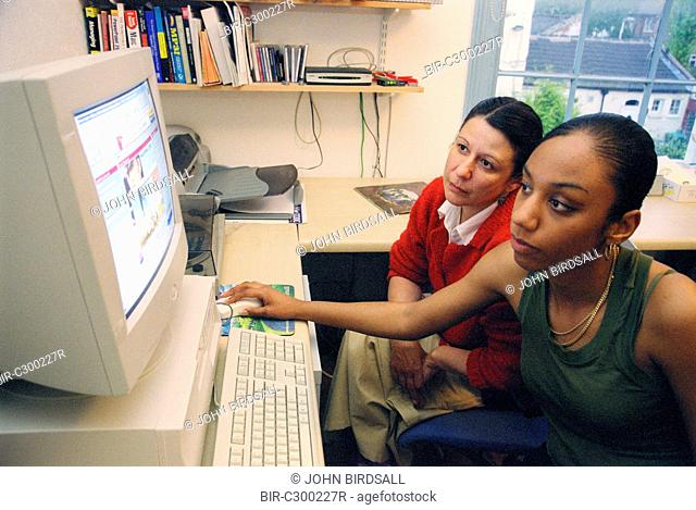 Single mother and teenage daughter using computer