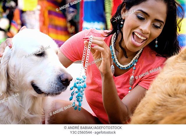Hispanic woman trying on jewelry while playing with dogs at a street market in Puerto Vallarta, Mexico