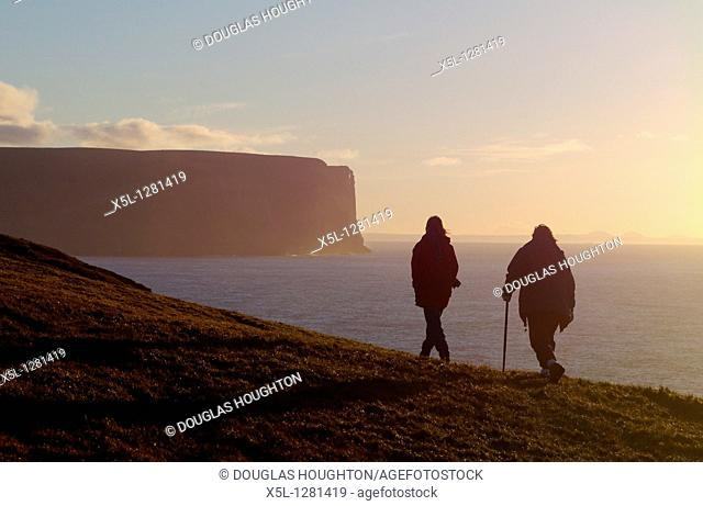 Black Craig STROMNESS AREA ORKNEY Two hikers on foot path Seacliffs and North Altantic Ocean dusk sunset