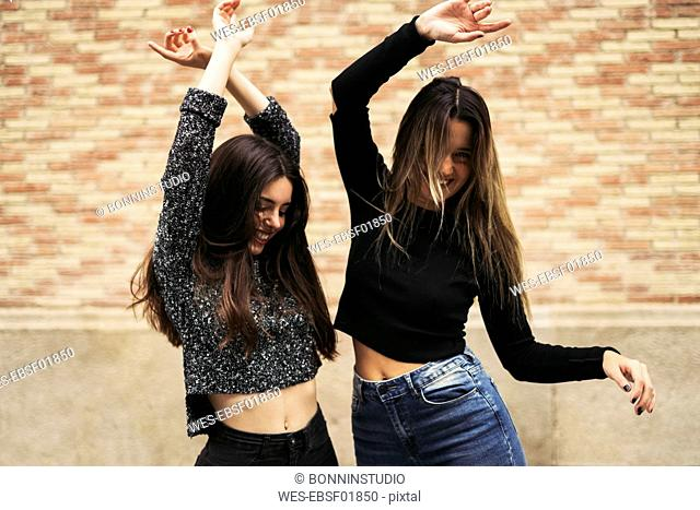 Girl friends dancing happily in the city