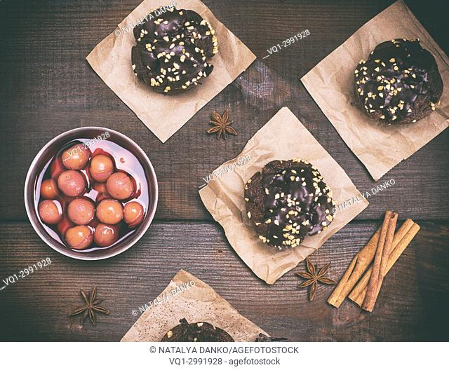 chocolate muffins and a plate of cherries in their own juice on a brown wooden background, top view, vintage toning