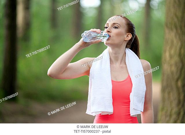 Woman drinking water during jogging in forest