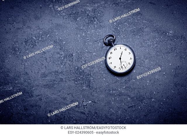 Old pocket watch on stone table in darkness. Symbol of time, deadline and nostalgia