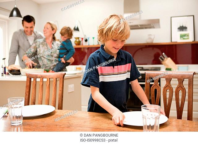 Son helping to lay table with parents and brother visible behind in kitchen