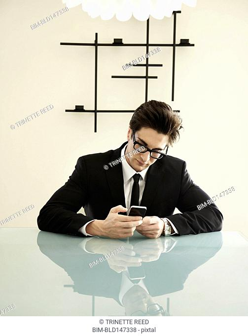 Trendy Caucasian businessman sitting at conference table looking at cell phone