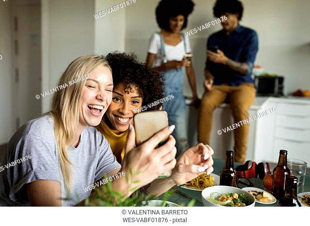 Happy girlfriends with cell phone sitting at dining table