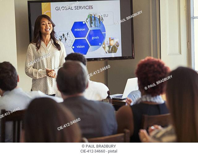 Smiling businesswoman leading business conference presentation at television screen