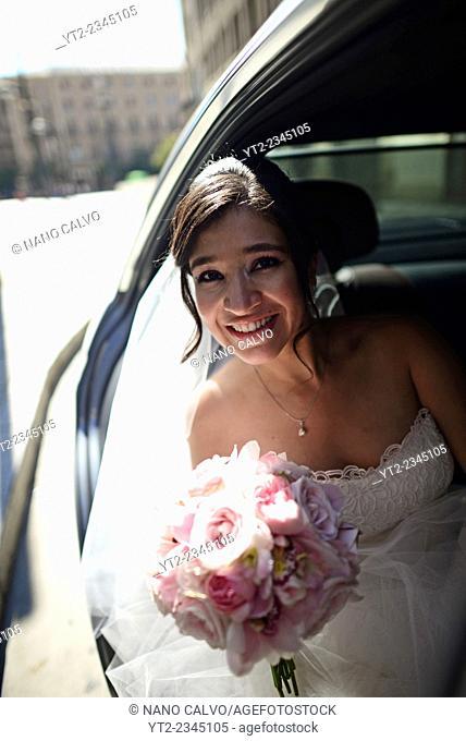 Latin bride in wedding car with flower bouquet