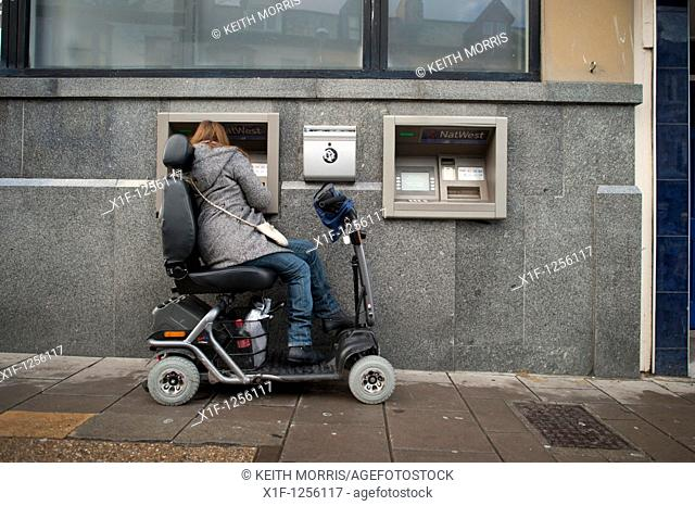 a woman in a powered wheelchair scooter using an ATM cash machine, UK