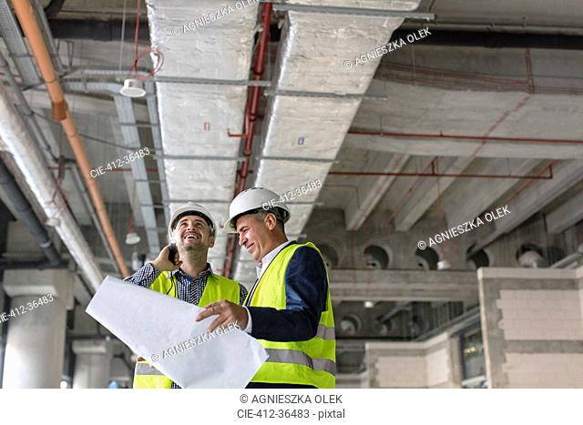 Male engineers with flashlight and blueprints at construction site