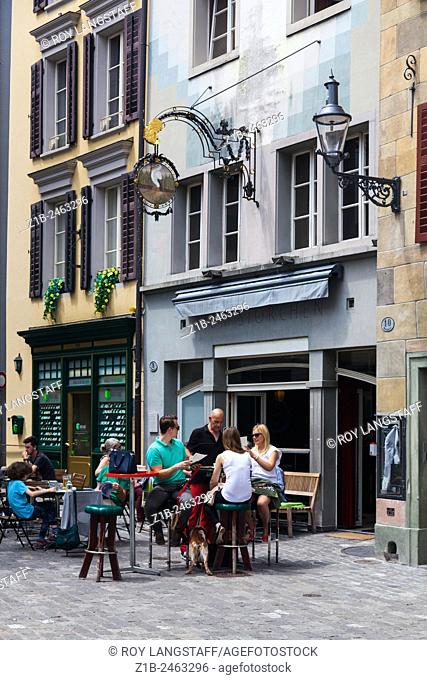 People relaxing with a drink on a warm Sunday morning in the old town of Lucerne, Switzerland