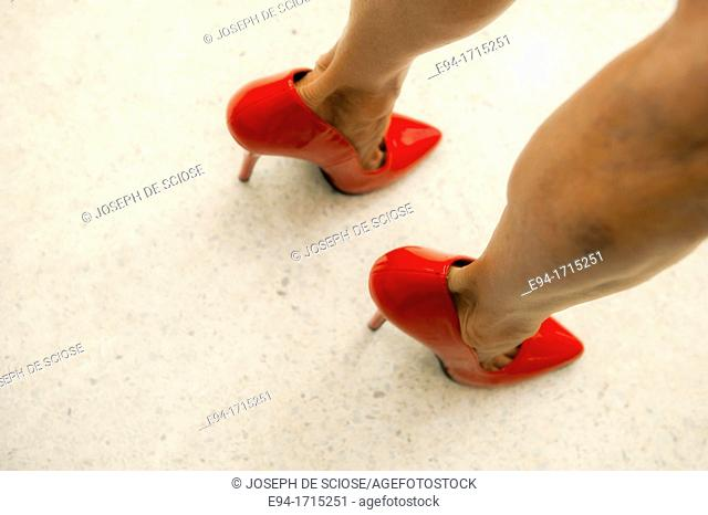 Close shot of a woman's legs with red high heels
