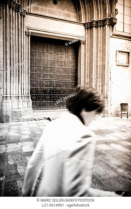 Woman walking in a street. Santa Maria del Mar Church. Ribera quarter, Barcelona, Catalonia, Spain