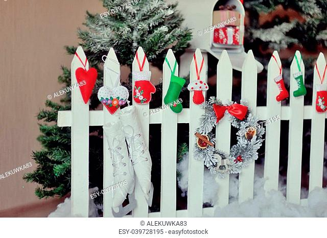 Christmas arrangements, trees and snow on a white fence hang different toys, sleigh and gifts