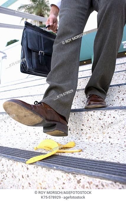 Businessman about to slip on banana peel