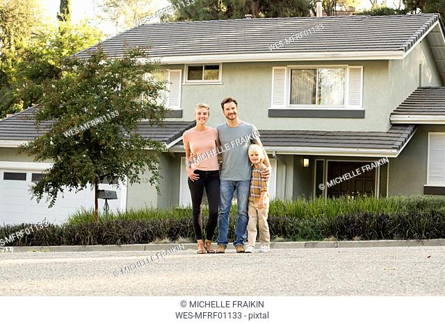 Portrait of smiling parents with boy standing in front of their home