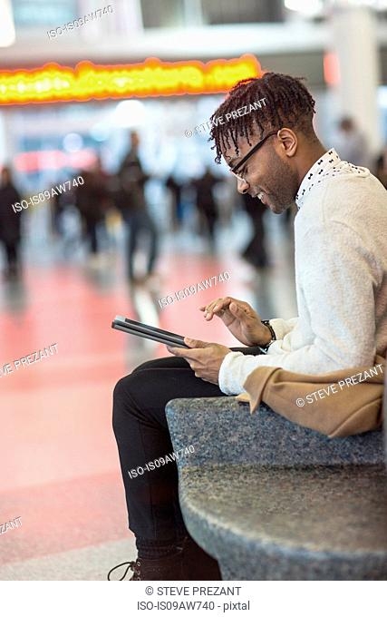 Young man sitting in train station using digital tablet touchscreen