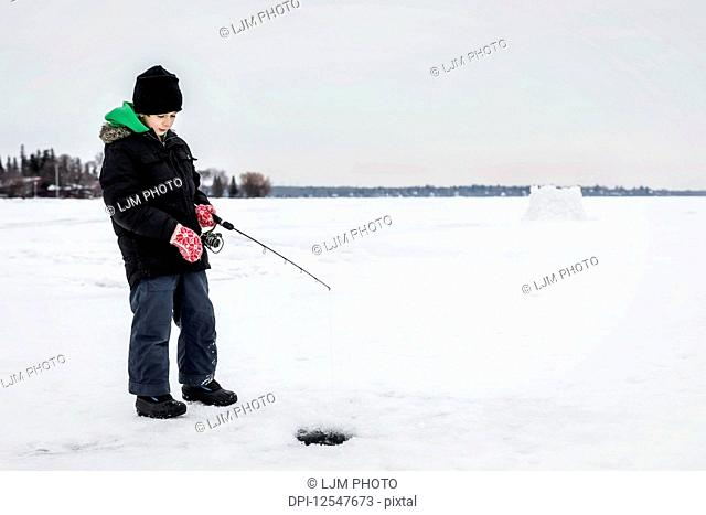 Boy patiently waiting for a bite while ice fishing at Wabamun Lake; Wabamun, Alberta, Canada