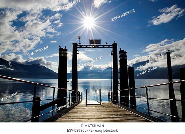Harbor on an alpine lake with mountains and clouds