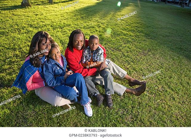 Portrait of African American family sitting in park, looking at camera