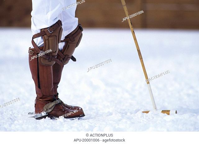 Snow polo player holding a mallet