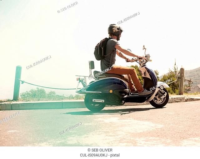 Mid adult man riding moped, rear view