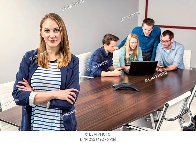 Young millennial businesswoman posing for the camera in a conference room of young professionals working together in a modern place of business; Sherwood Park