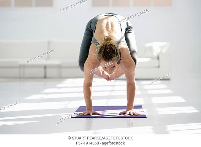 Healthy young woman doing the crane pose yoga position