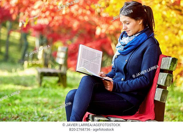 Woman reading a book in the park, Trees in Autumn, Pagoetako Parke Naturala, Pagoeta Natural Park, Aya, Gipuzkoa, Basque Country, Spain