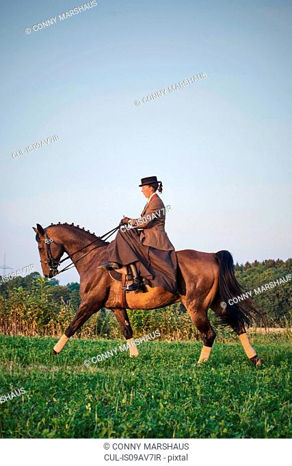 Woman riding and training dressage horse in field
