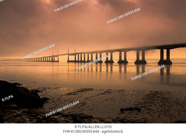 View of road bridge over river shrouded in mist at sunrise, viewed from Diver's Rock at Sudbrook, Second Severn Crossing, River Severn, Severn Estuary