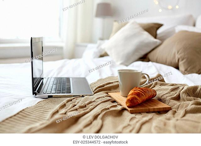 technology, holidays, christmas, interior and winter concept - cozy bedroom with laptop computer, coffee cup and croissant on bed at cozy home