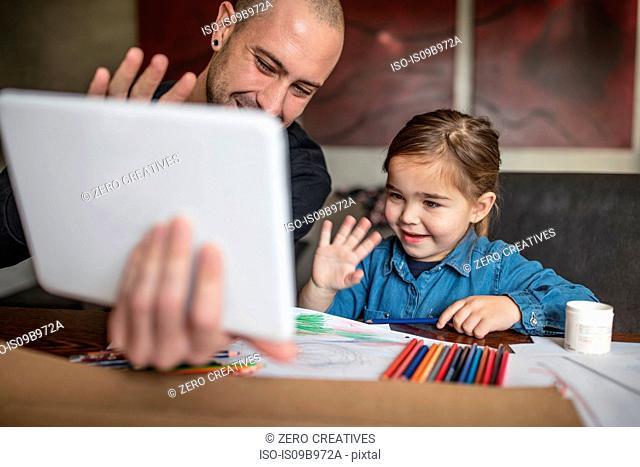 Man and daughter at table waving at digital tablet