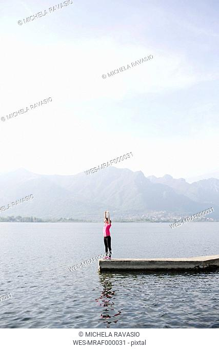 Italy, Lecco, young woman stretching at the lake