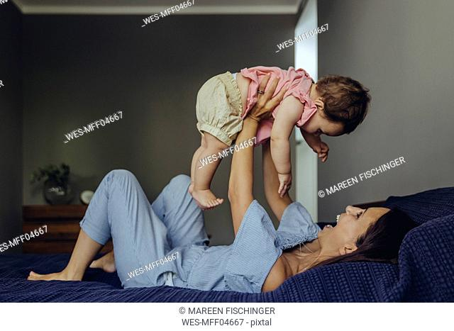 Happy mother lifting up her baby girl on bed
