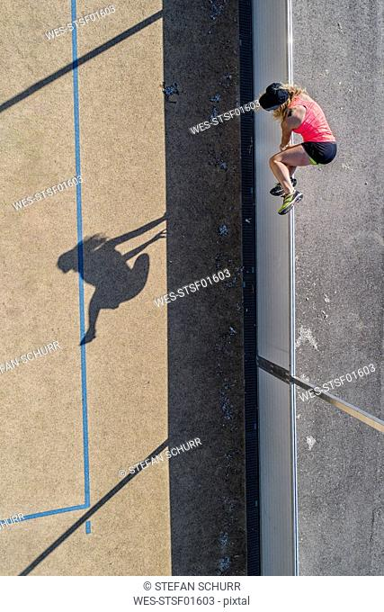 Aerial view of sportive woman jumping over barrier