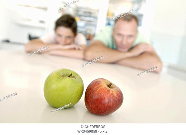 Mature man and his son leaning over a table and looking at apples