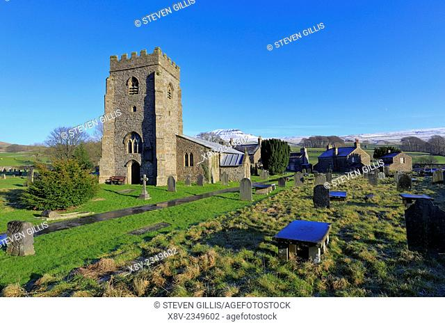 St Oswald's Church with snow on Pen-y-ghent, Pennine Way, Horton in Ribblesdale, Yorkshire Dales National Park, England, UK