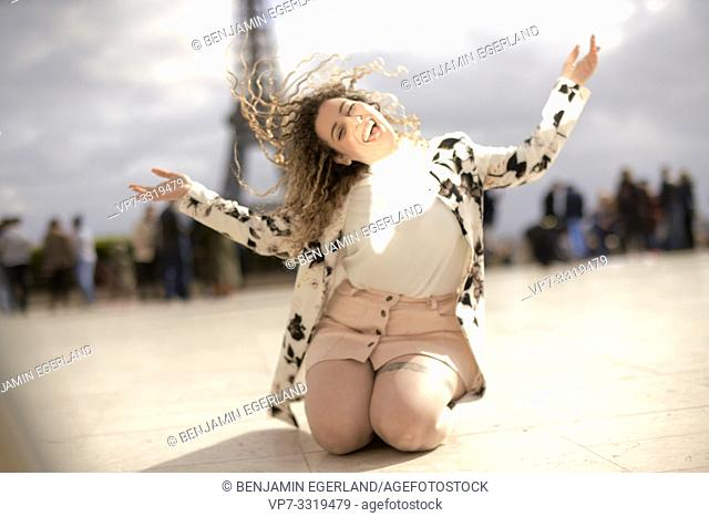 lively woman kneeling and dancing outdoors in public in city next to tourist sight Eiffel Tower, happy, at Espl. du Trocadéro, in Paris, France