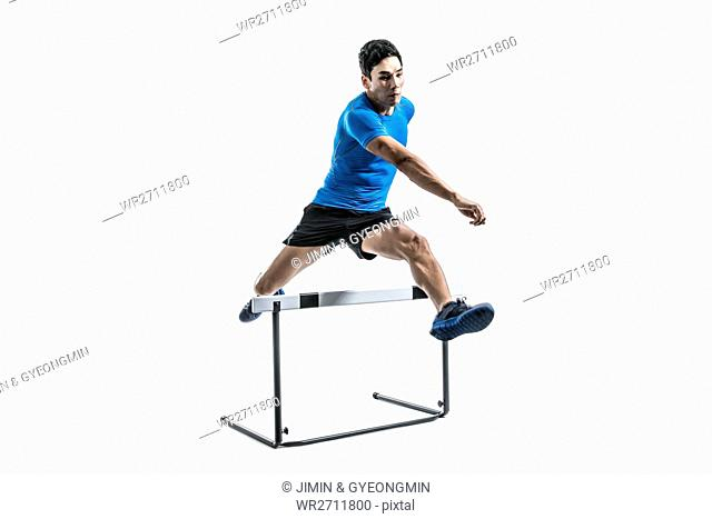 Male athlete jumping over obstacle
