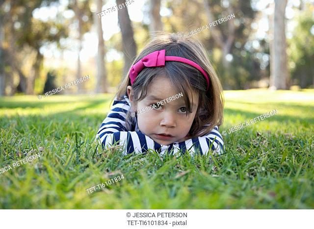 Portrait of sad girl (4-5 years) lying on grass in park
