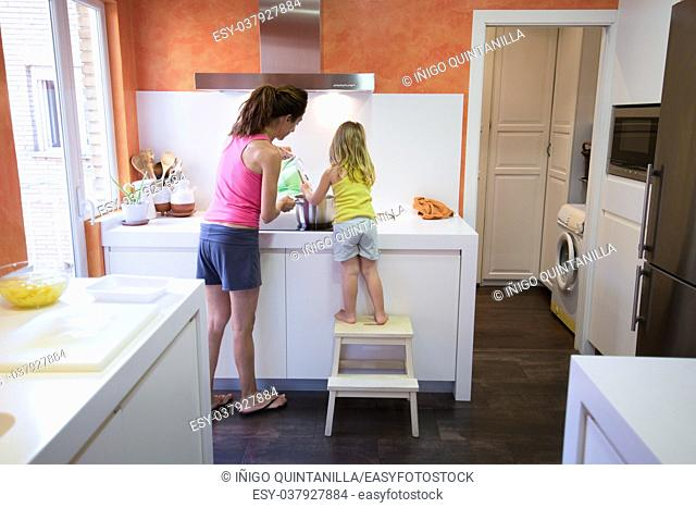 Back of woman mother and four years old blonde child on stool o ladder in the kitchen cooking together as a team, in electrical cooktop with a saucepan