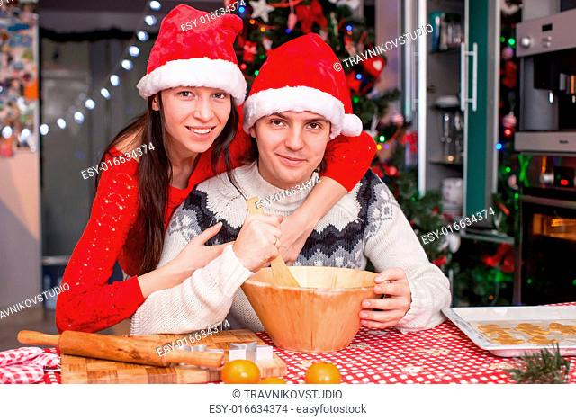 Portrait of young happy couple baking Christmas cakes at home in Santa hat