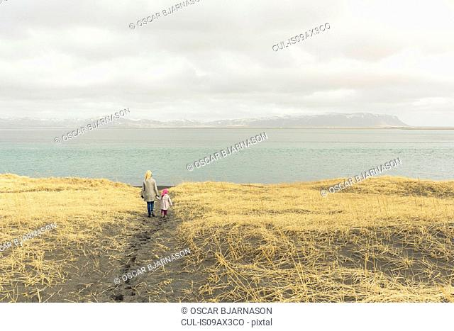 Mother and daughter, holding hands, walking towards beach, rear view, Eyrarbakki, Iceland