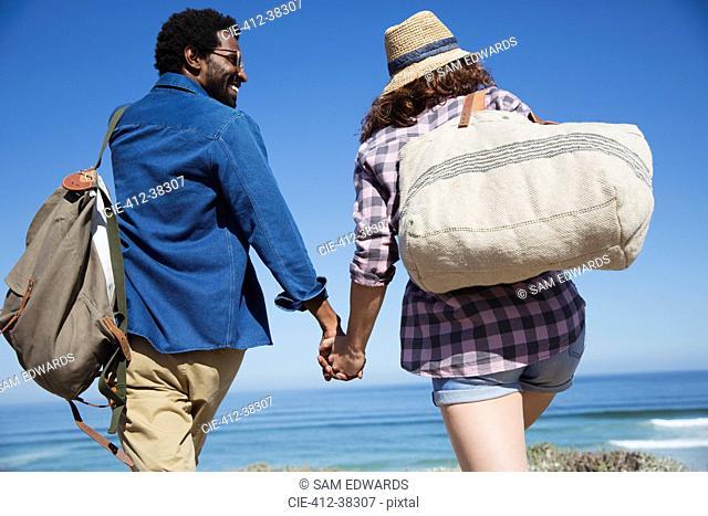 Multi-ethnic couple holding hands, walking on sunny summer ocean beach
