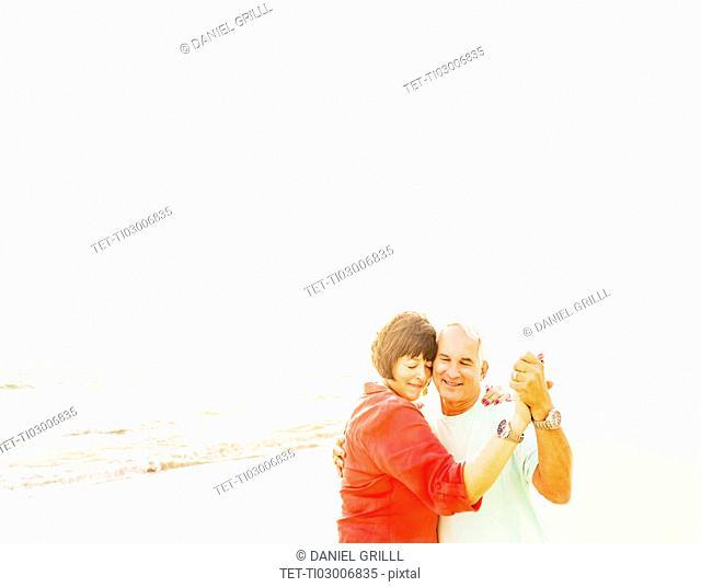 Couple dancing on beach at sunrise