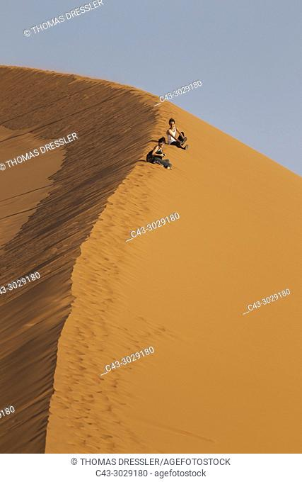 Tourists having fun at Dune 45 in the Namib Desert. This is probably the worlds most photographed and climbed dune. Namib-Naukluft National Park, Namibia