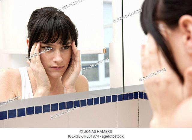 This picture shows a young caucasian woman with brown hair as she watches her reflection in bathroom mirror
